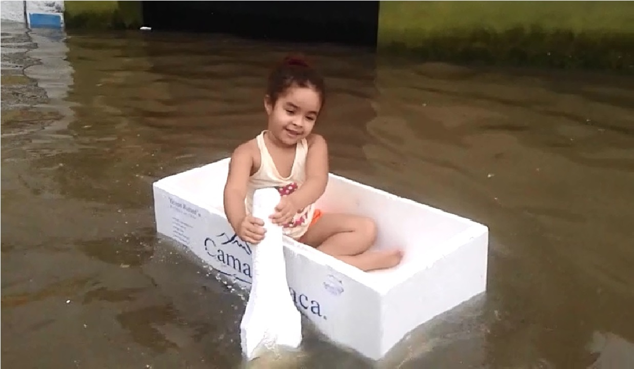 Maria Laís, de apenas quatro anos, aproveita o alagamento de sua rua para brincar de barquinho (FOTO: Reprodução vídeo)